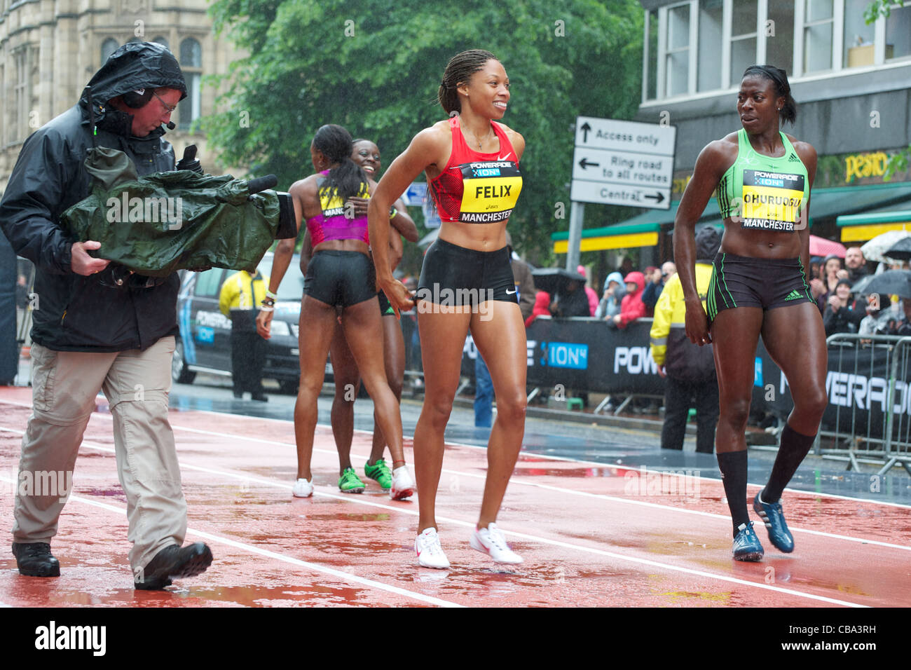 Allyson Felix and Christine Ohuruogu converse in the rain after running in the Great City Games 2011, Manchester - Stock Image