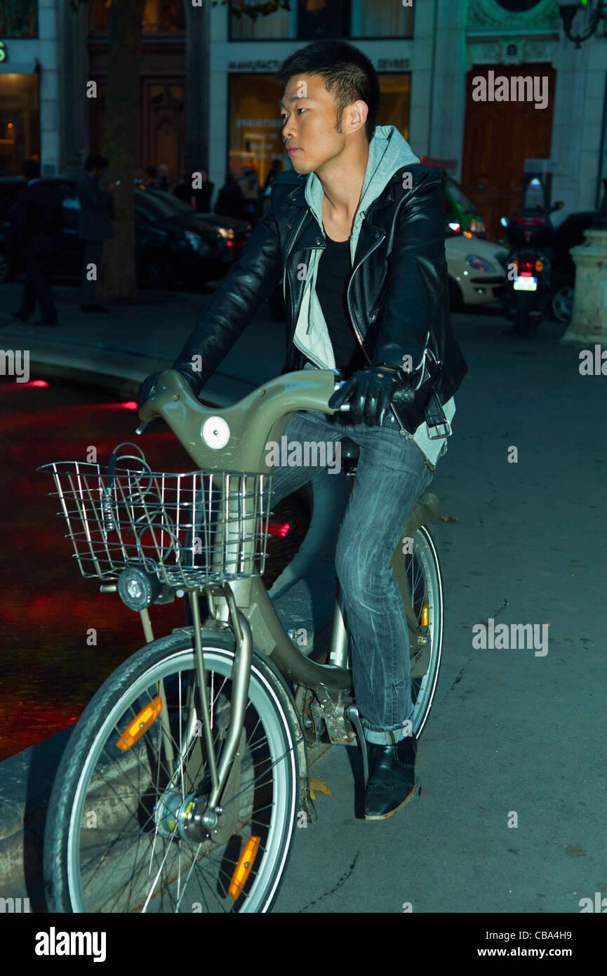 Paris, France, Young Chinese Man Using Free Velib Bicycle, Cycling at Night Stock Photo