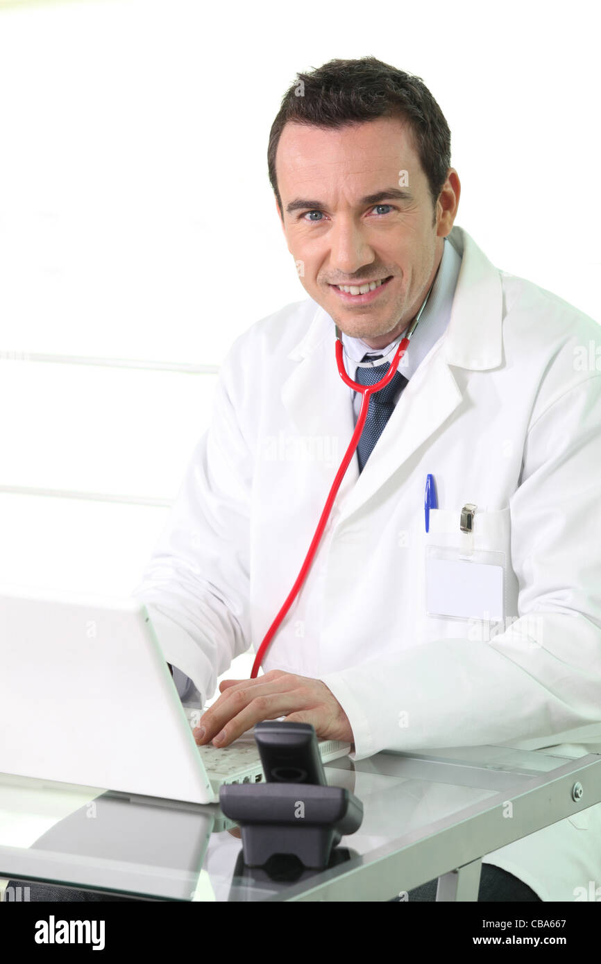 Doctor working on his laptop - Stock Image