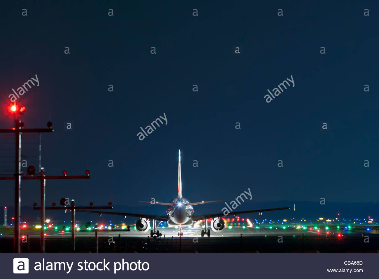 night airport starting twin-jet airliner Airbus runway illumination landing lights darkness noise Duesseldorf Germany - Stock Image