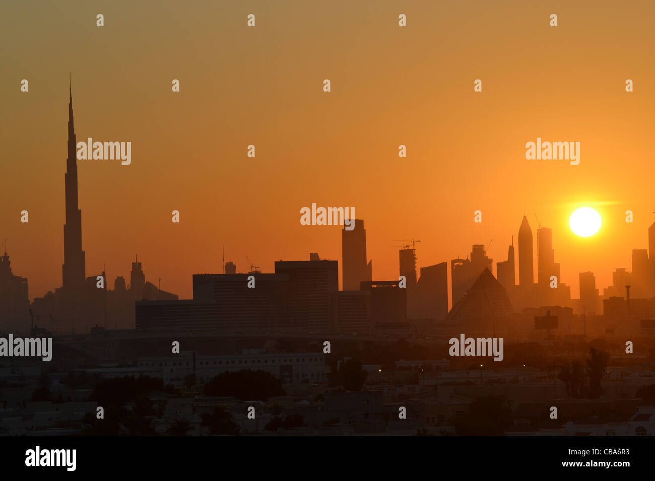 Dubai skyline at sunset with Burj Khalifa on left. - Stock Image