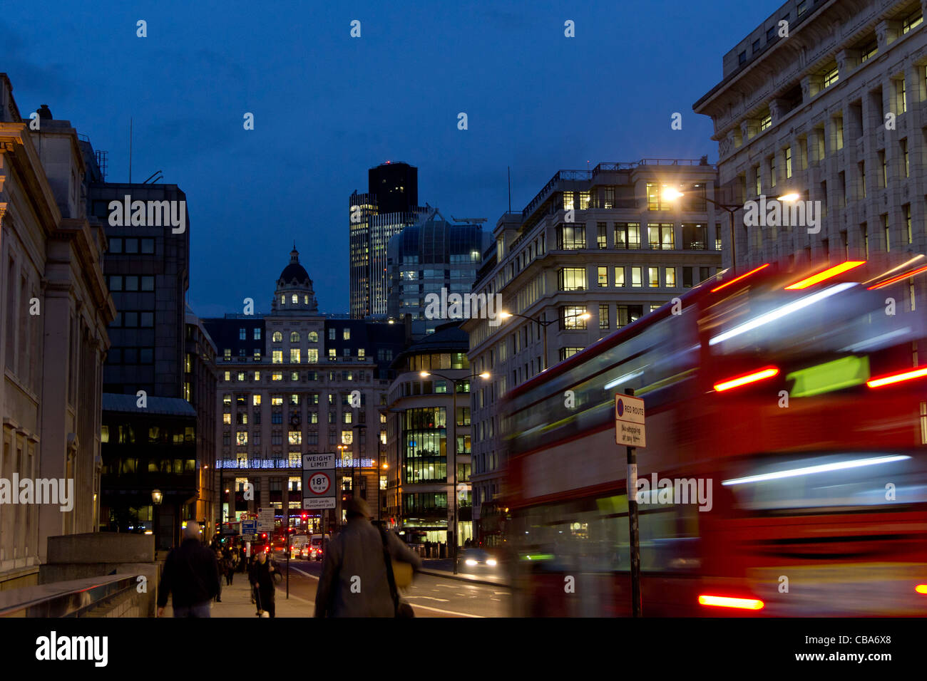 View along King William Street from London Bridge of workers walking home at nightfall and blurred motion London Stock Photo