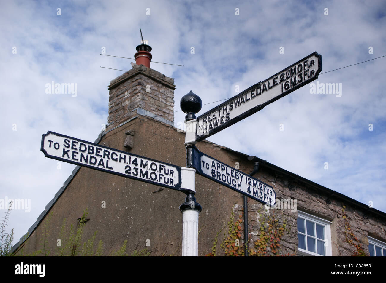 Road sign showing distances in miles and furlongs, Kirkby Stephen, Cumbria, England Stock Photo