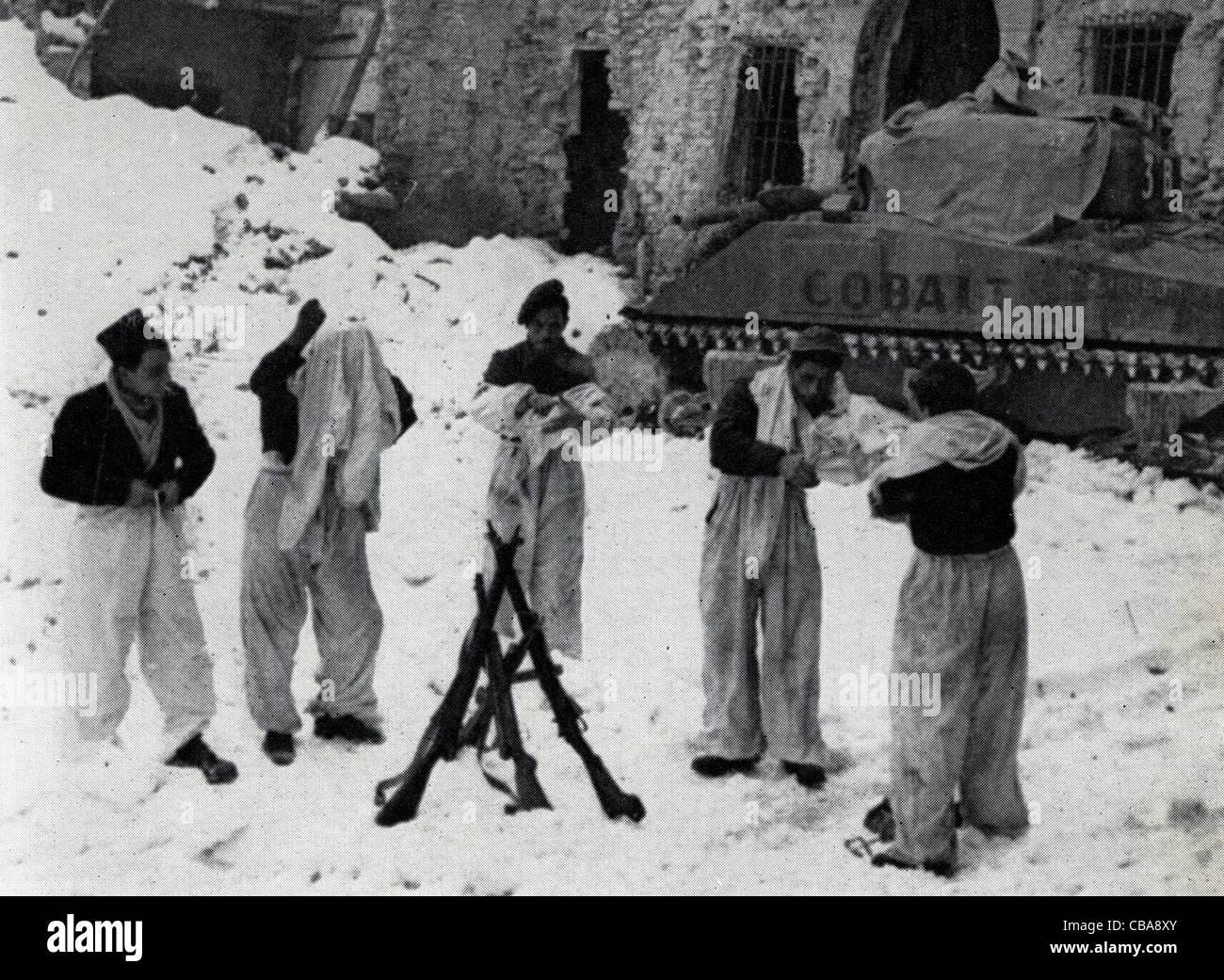 British infantry don snow camouflage uniforms alongside a Sherman tank. Italy WW11. - Stock Image