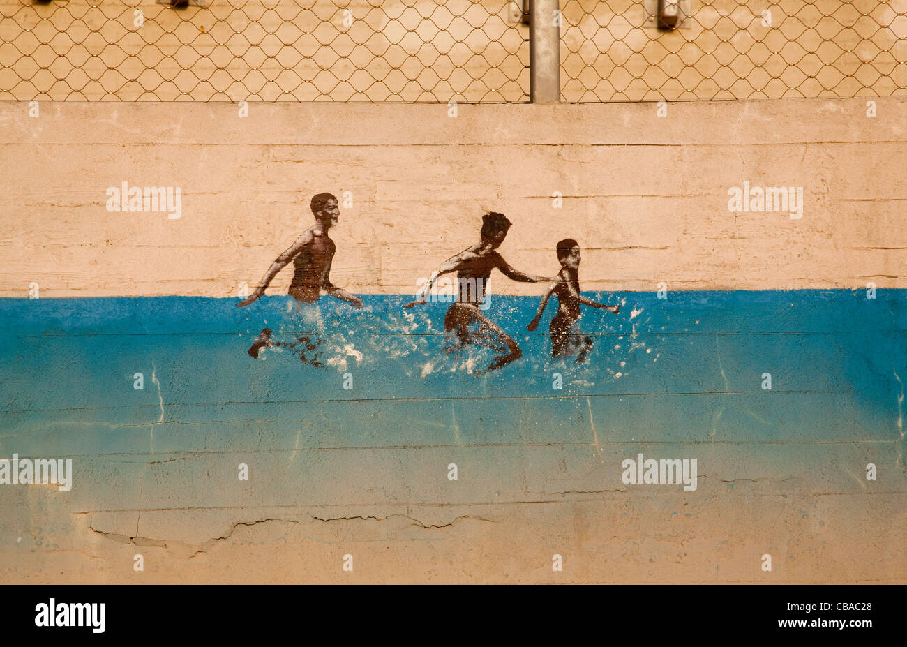 Wall painting of three adolescents splashing through sea in Tel Aviv Israel - Stock Image
