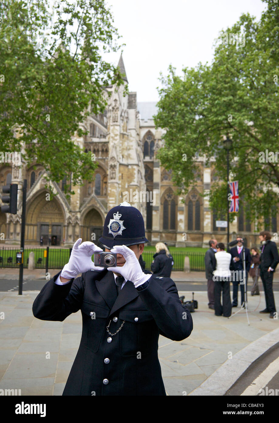 Police officer in Parliament Square taking photos of crowds outside Westminster Abbey during the marriage of Prince - Stock Image