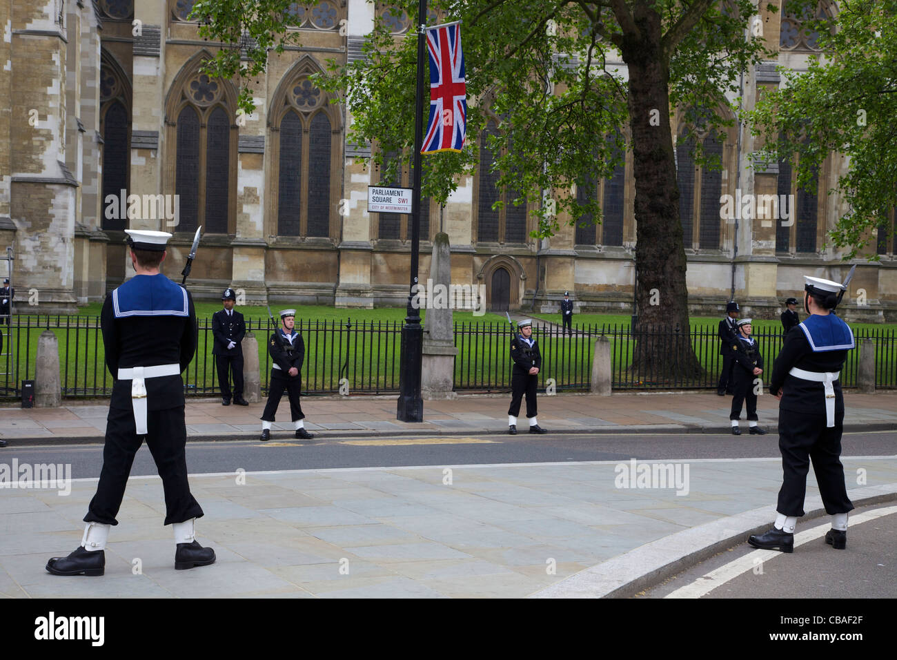 Members of the British Royal Navy and Metropolitan Police stand guard outside Westminster Abbey, marriage of Prince - Stock Image