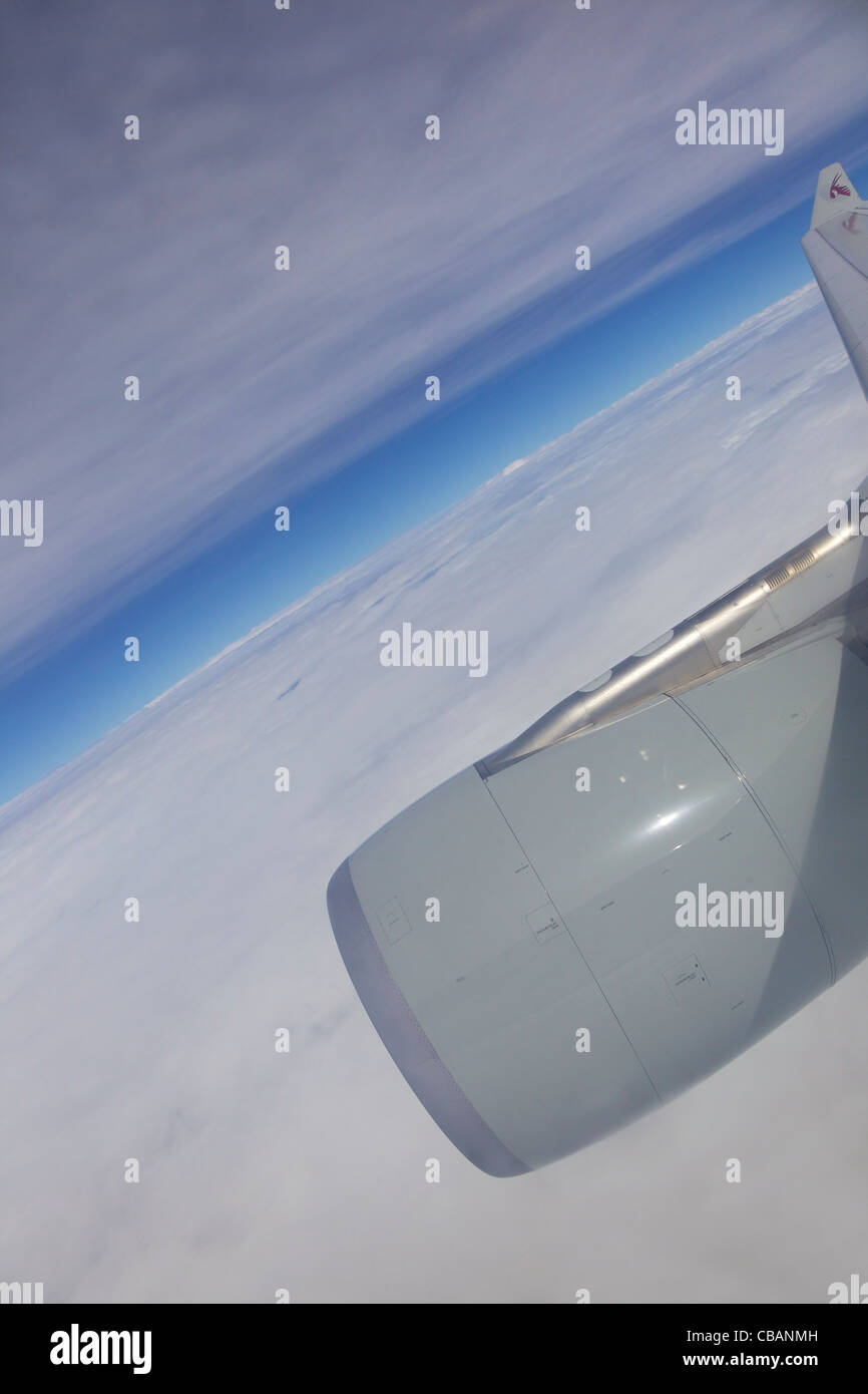 View through  passenger jet window of Qatar airliner wing, sky and clouds - Stock Image