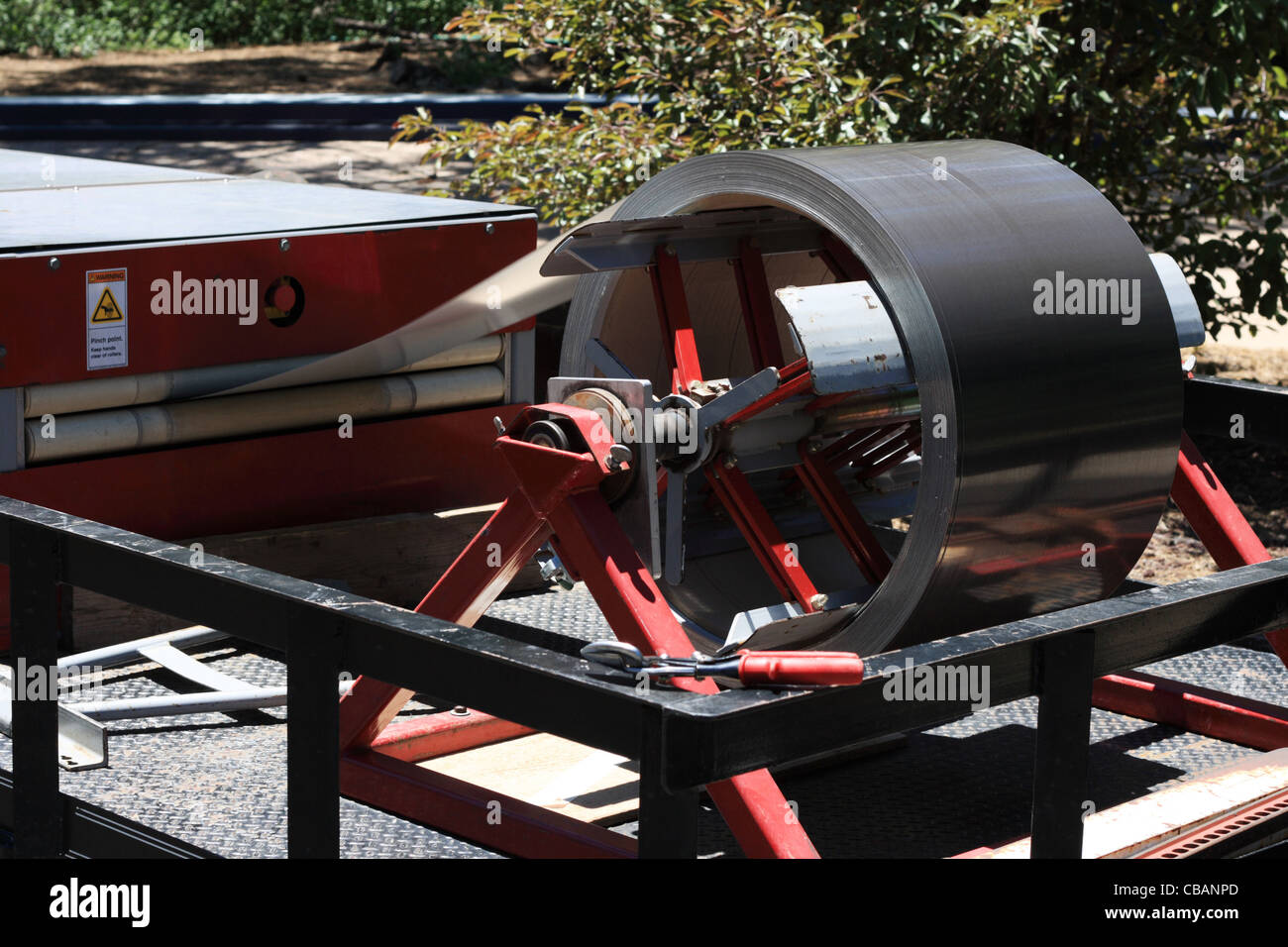 metal enters a machine for folding sheet metal into metal roofing - Stock Image