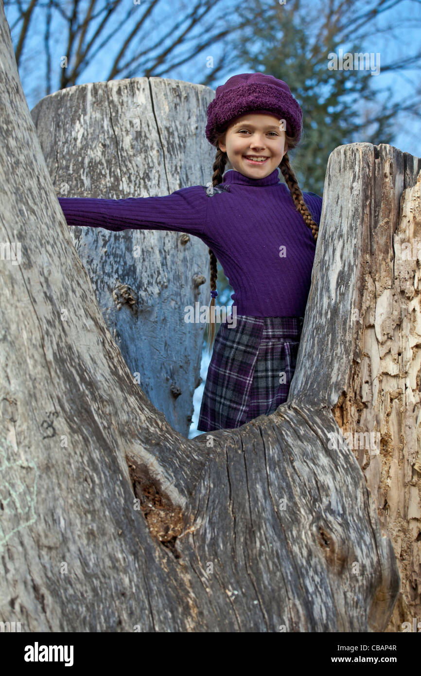 Girl climbs in the fall on an old tree stump - Stock Image