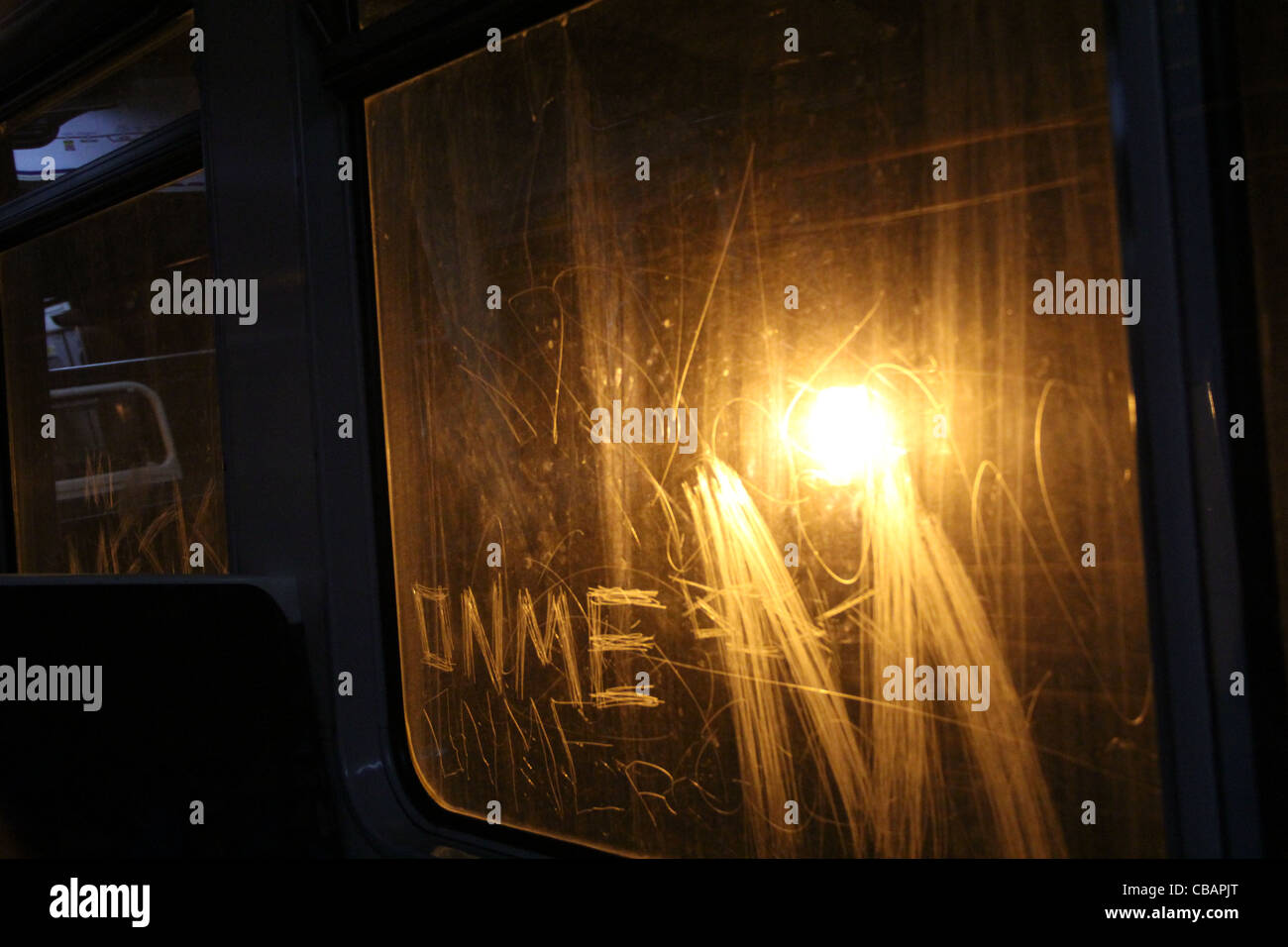 View from inside tube carriage looking towards a light which illuminates graffiti on the train window. Vandalism - Stock Image