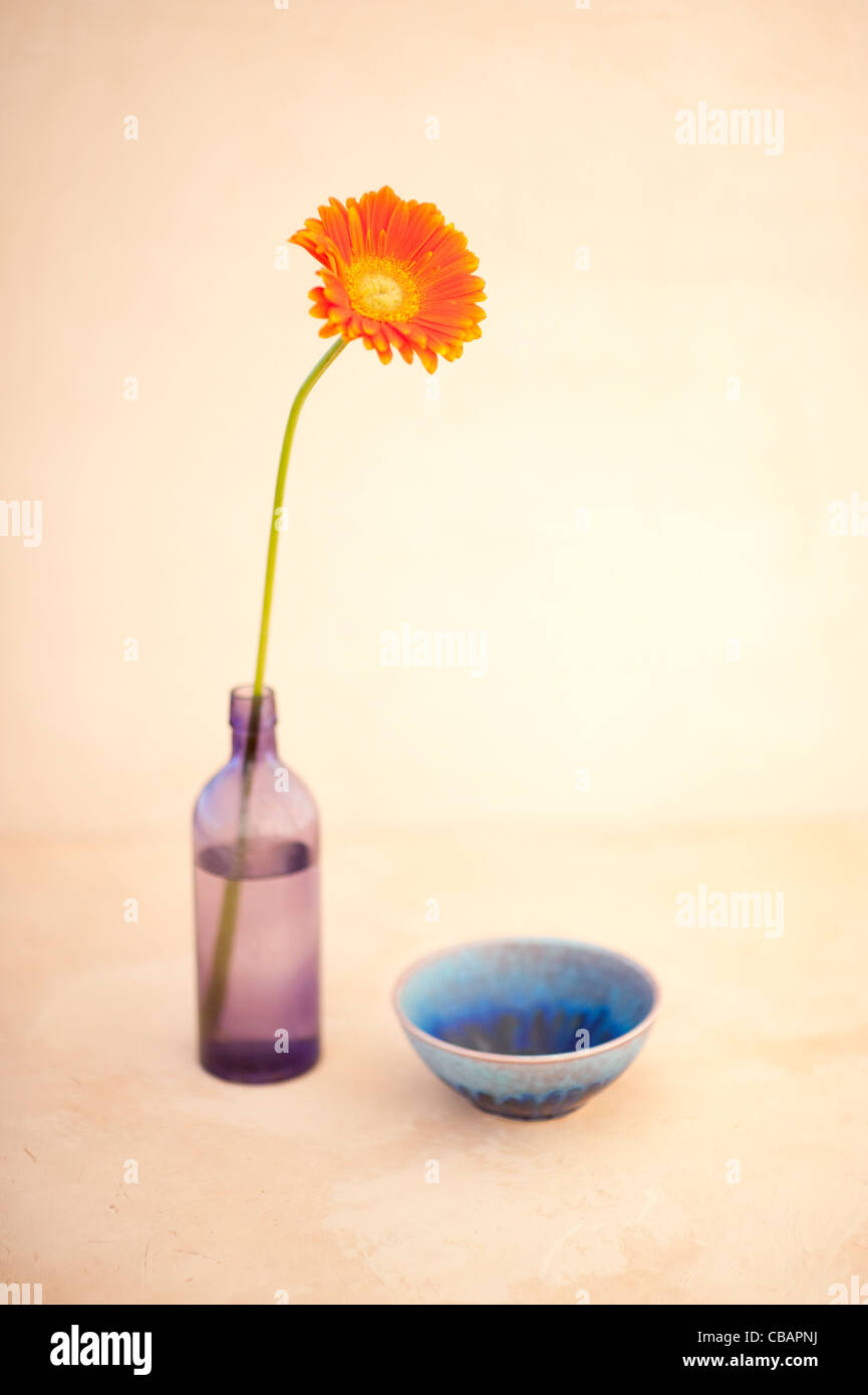 A flower, old purple glass bottle, and blue hand crafted ceramic bowl. - Stock Image