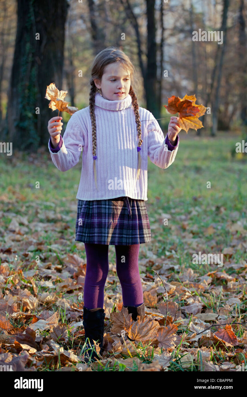 girl is playing in the woods with autumn foliage - Stock Image