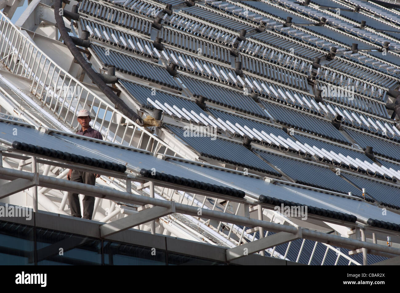 A worker on the roof of the Micro-E Hotel, world's largest solar powered hotel. China Solar Valley, Dezhou, - Stock Image