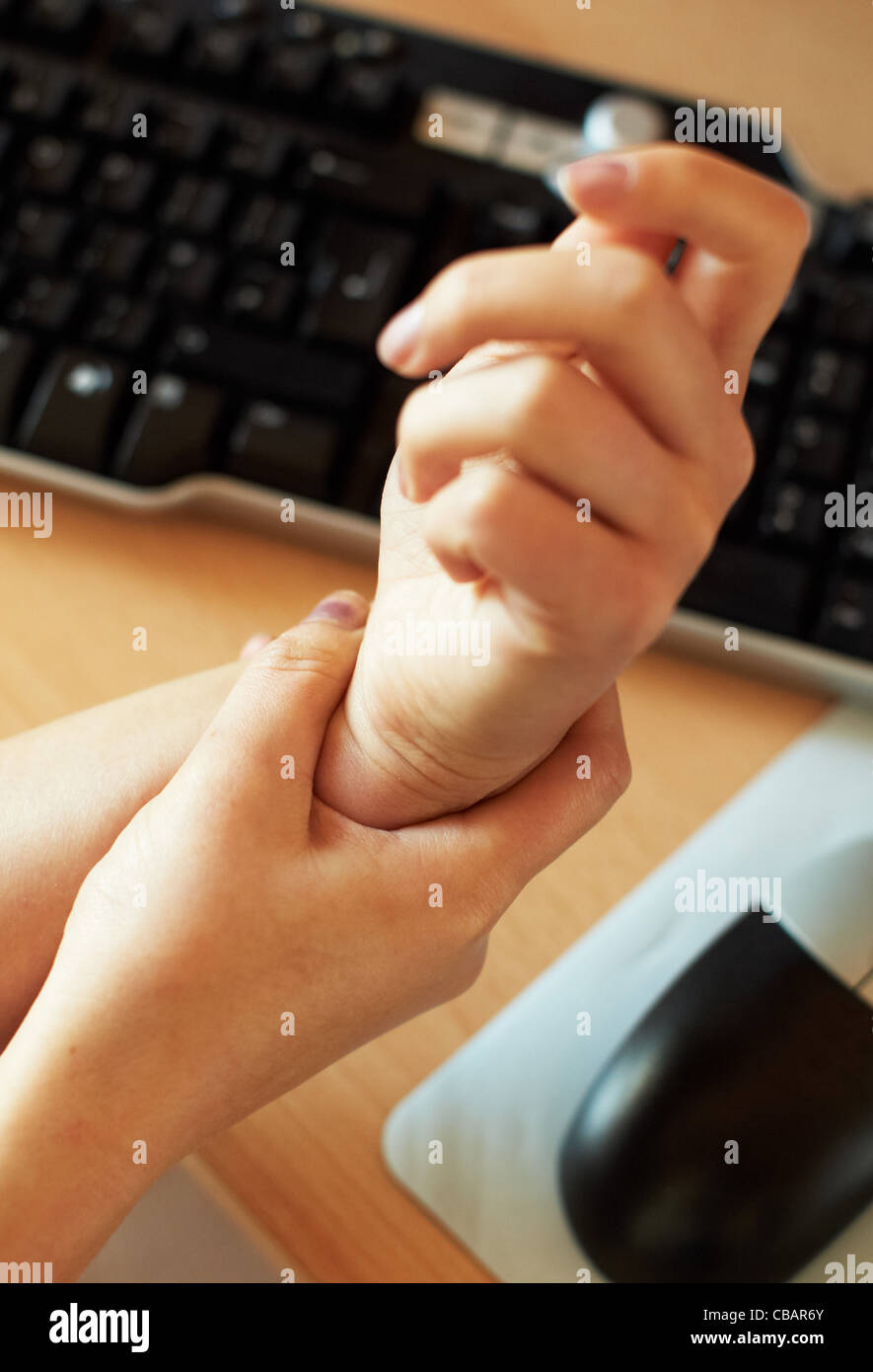 Woman massaging wrist - Stock Image