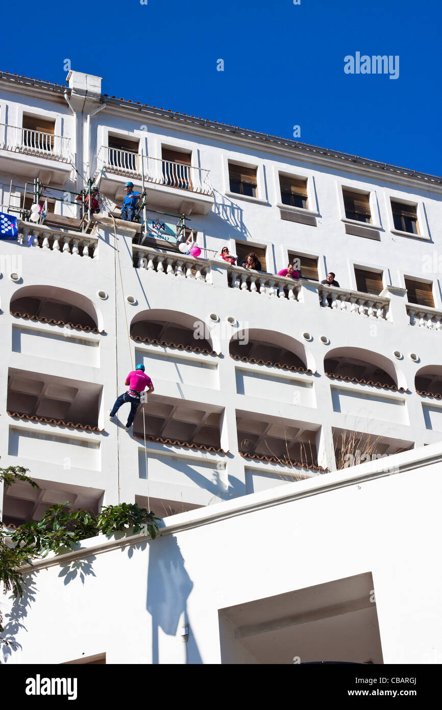 A man rappels a building for charity, Main Street, Gibraltar. - Stock Image