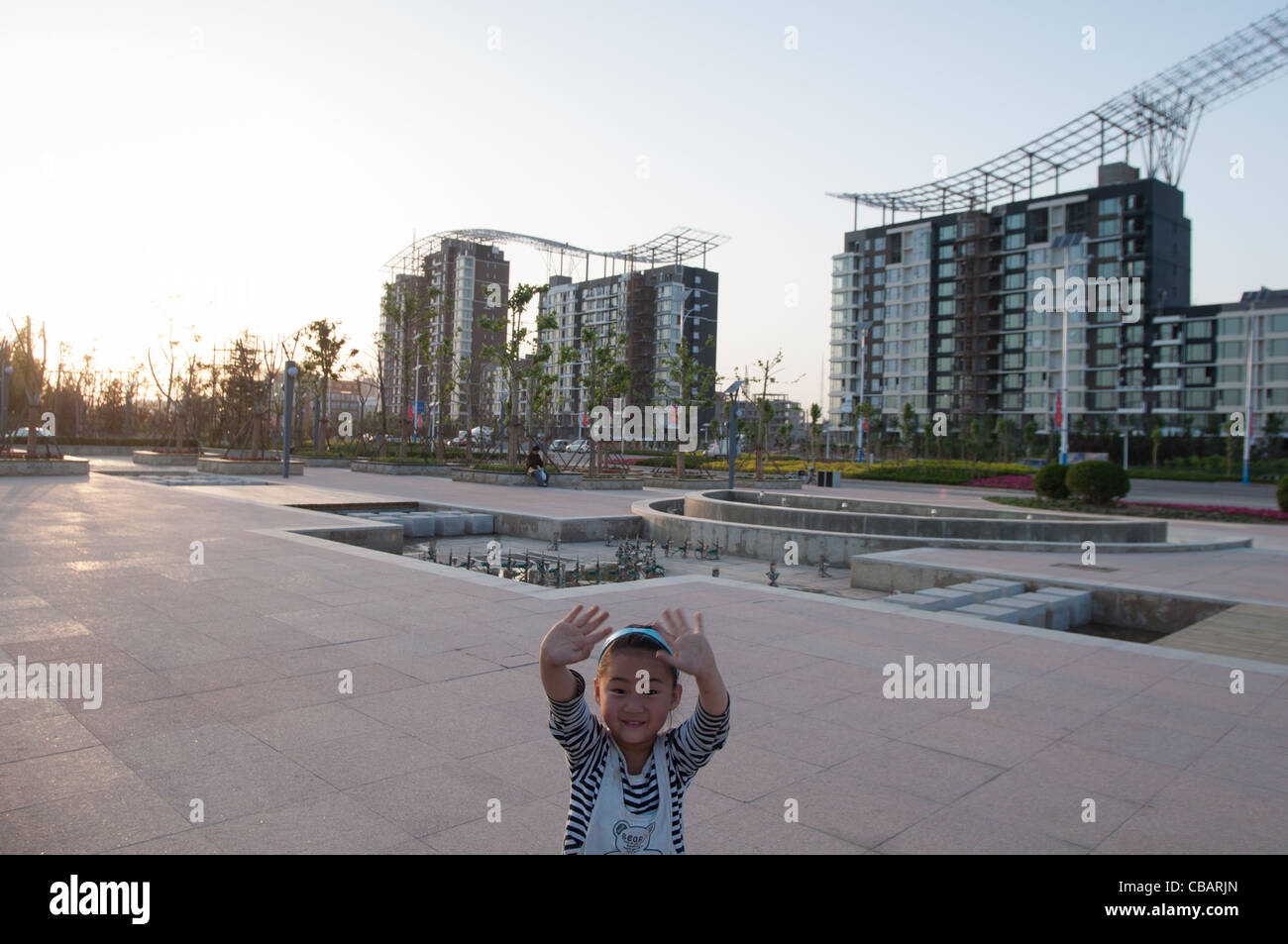 A child in front of a group of buildings under construction. Dezhou, Shandong, China - Stock Image