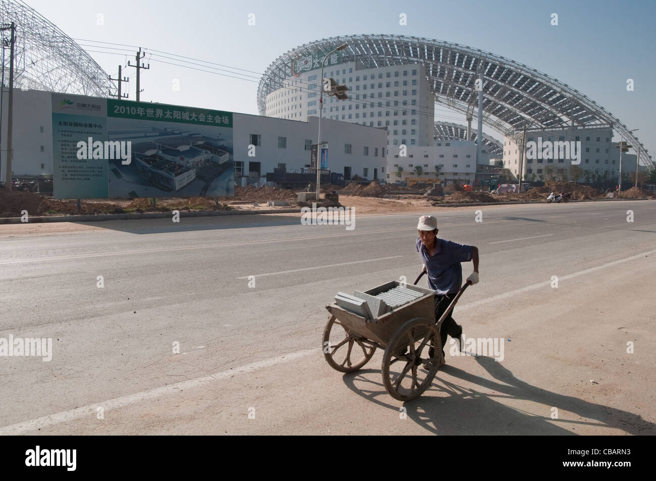 A worker with a wheelbarrow goes to the construction site of a new building of the China Solar Valley. Dezhou, Shandong, - Stock Image