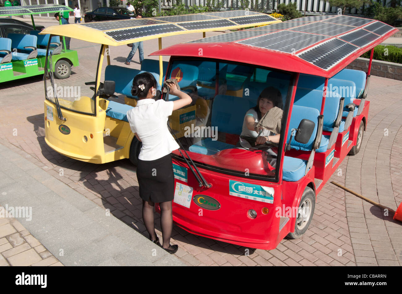 Two hostess set up a solar powered bus. China Solar Valley, Dezhou, Shandong, China - Stock Image