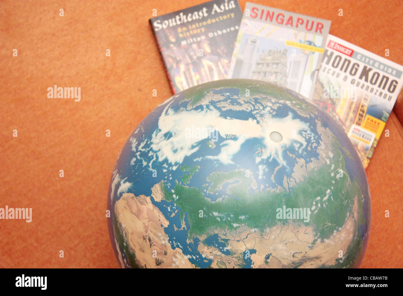 Globe with travel guide books - Stock Image