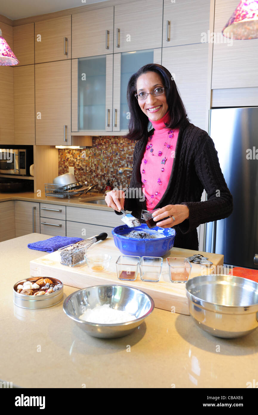 Celebrity chef, Carla Hall cooking in her home kitchen in Washington DC was on Top Chef on Bravo and is on The Chew - Stock Image