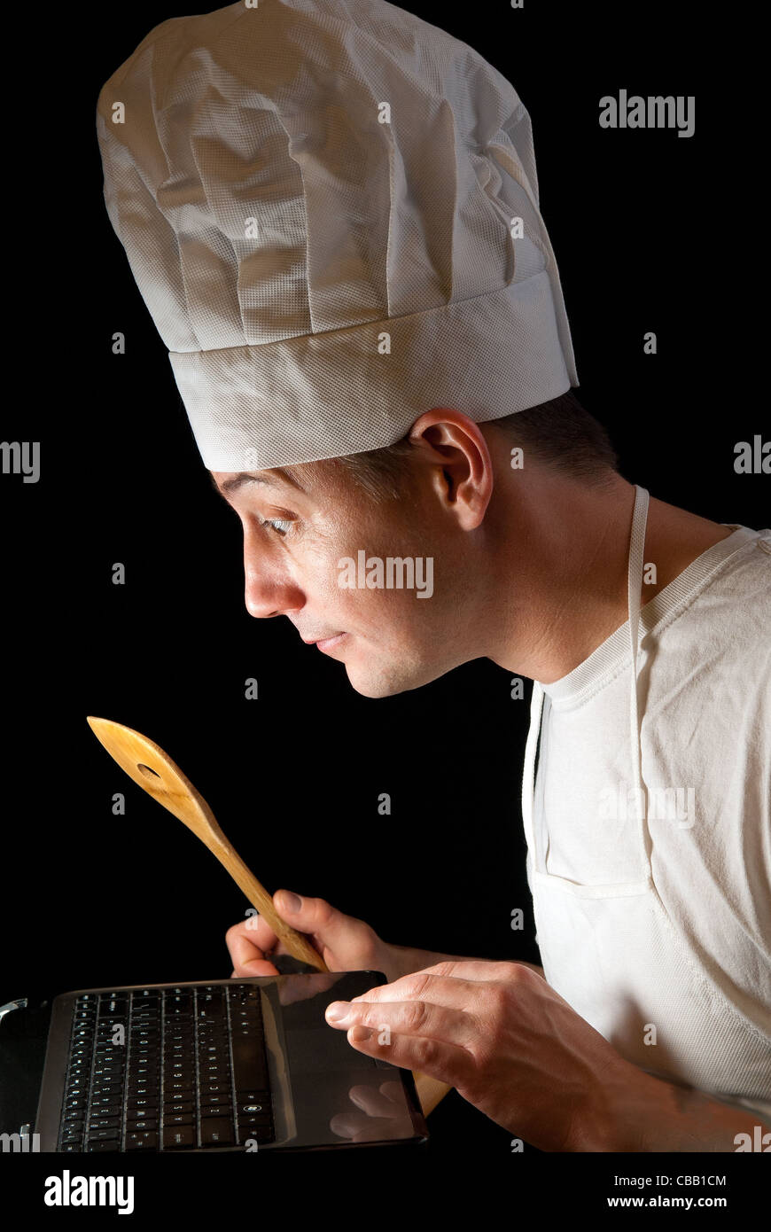 happy Chef with spatula using a computer to search for a recipe - Stock Image