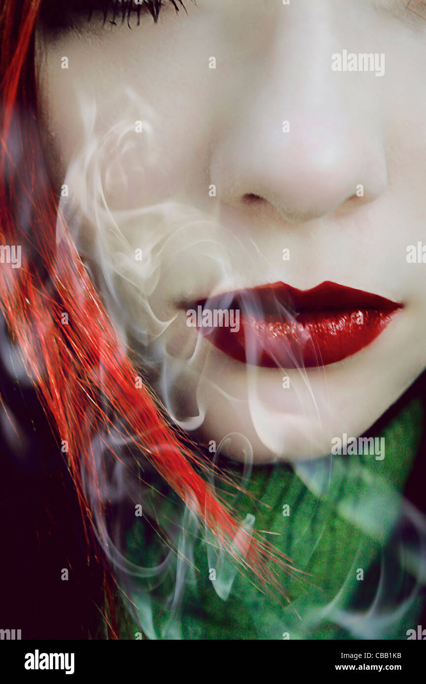 The bottom half of a women's face with smoke swirling around red lipstick. - Stock Image