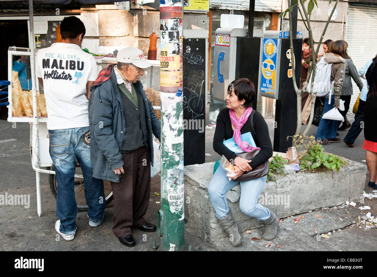 short kindly grandfatherly old man socializing with younger married woman on busy streetcorner Roma district Mexico - Stock Image