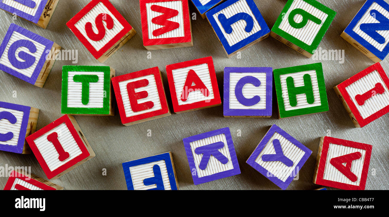 Wooden blocks forming the word TEACH in the center - Stock Image