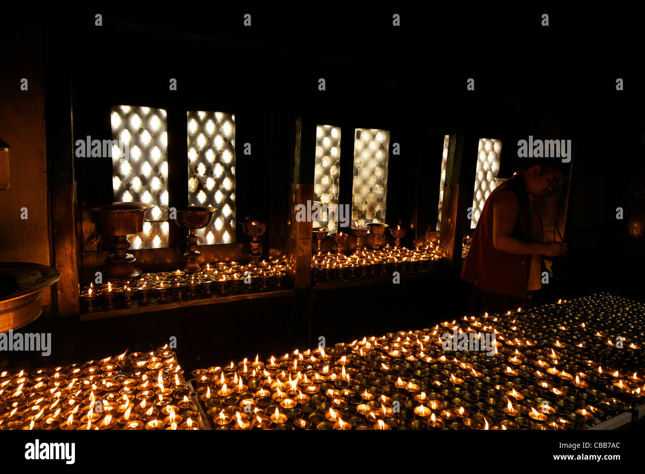 Buddhist monk lighting oil lamps Swayambhunath Stupa Monkey Temple UNESCO World Heritage Site Kathmandu Nepal Asia - Stock Image