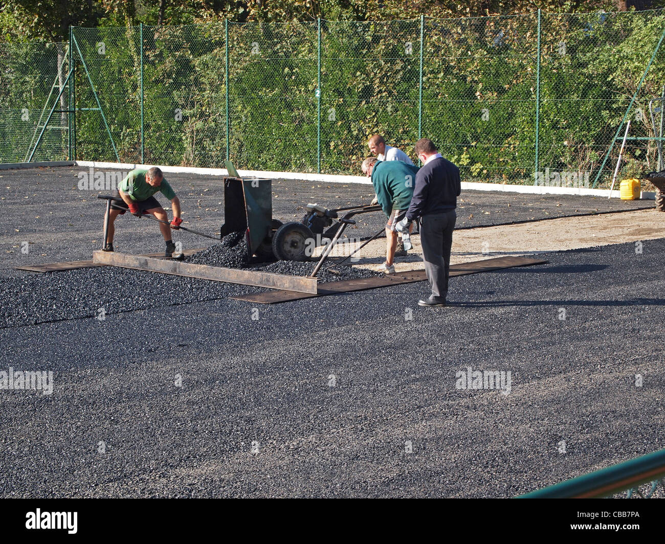Construction of synthetic clay tennis courts - the base macadam layer is being levelled and compacted - Stock Image