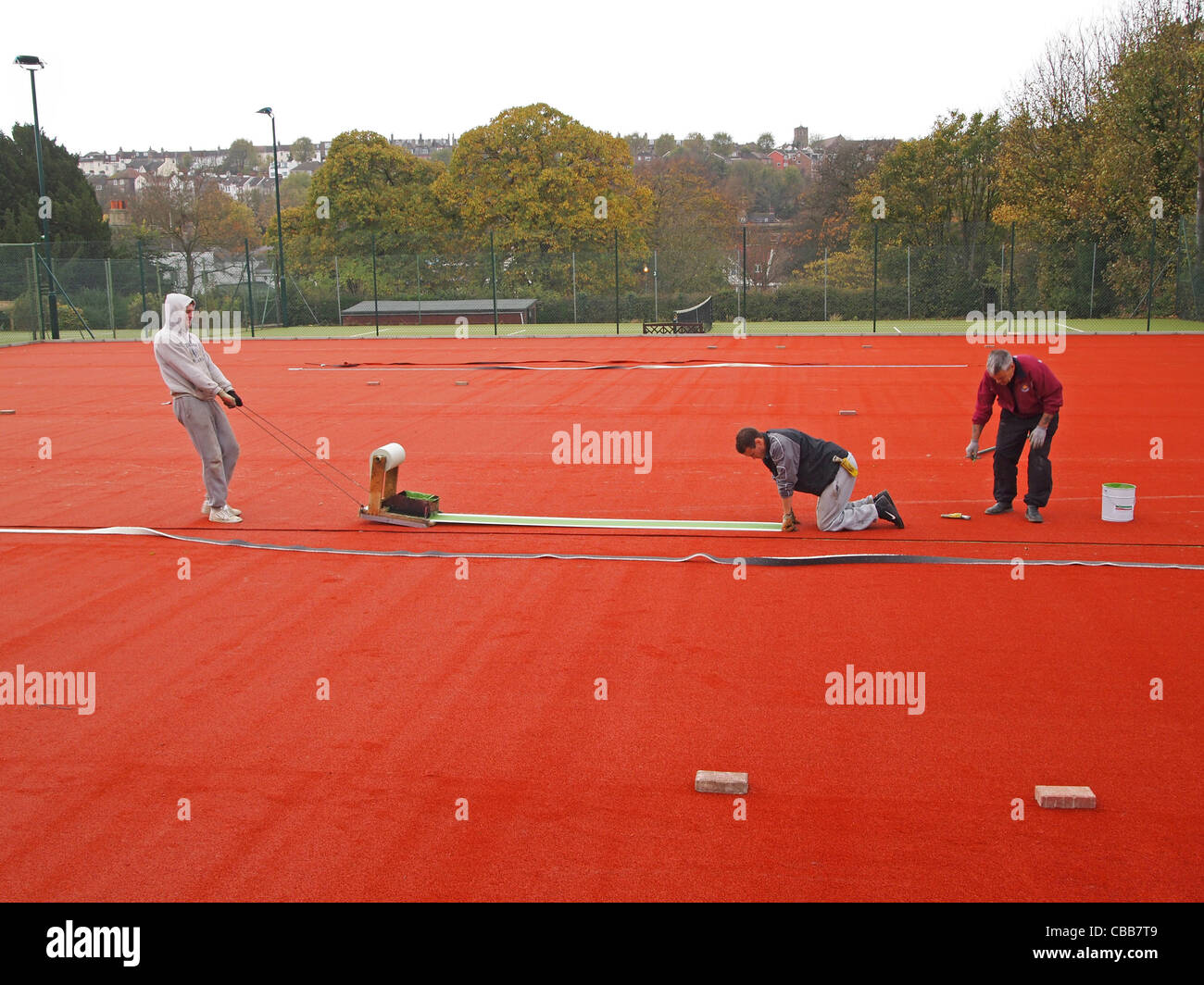 Construction of synthetic clay tennis courts - cutting in the white 'lines' into the stability base - Stock Image