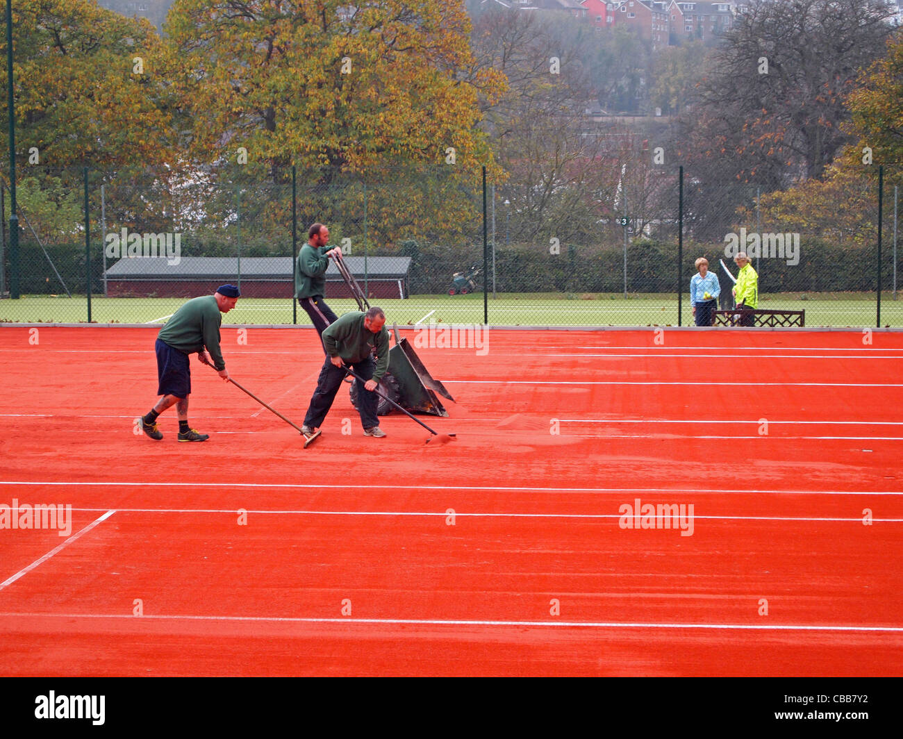 Construction of synthetic clay tennis courts - pouring and levelling the clay top surface on the stability mat - Stock Image