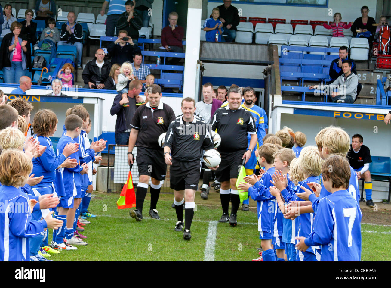 Referees and Teams walk out to applause from young footballers - Stock Image
