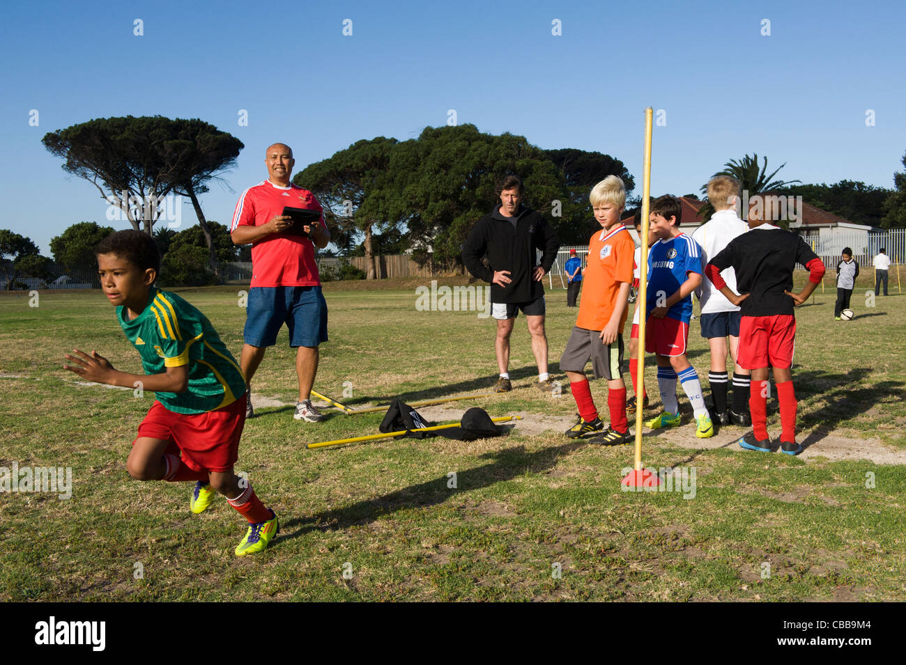 Football coach watching youth players exercising sprints Cape Town South Africa - Stock Image