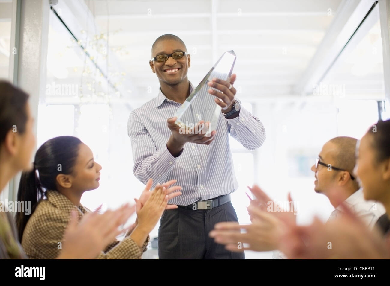 Businessman holding award in meeting - Stock Image