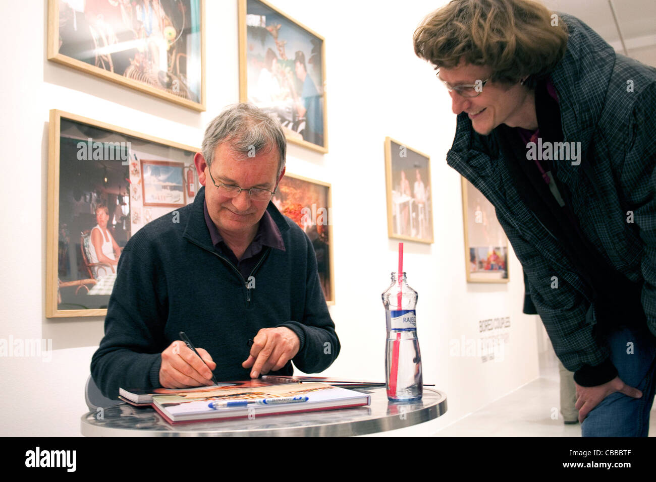 British photographer Martin Parr signs one of his books after his talk to the audience in frame of his solo show - Stock Image