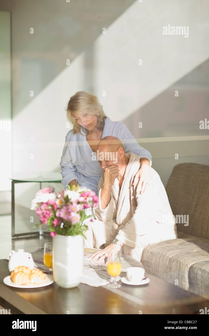 Stressed couple reading newspaper - Stock Image