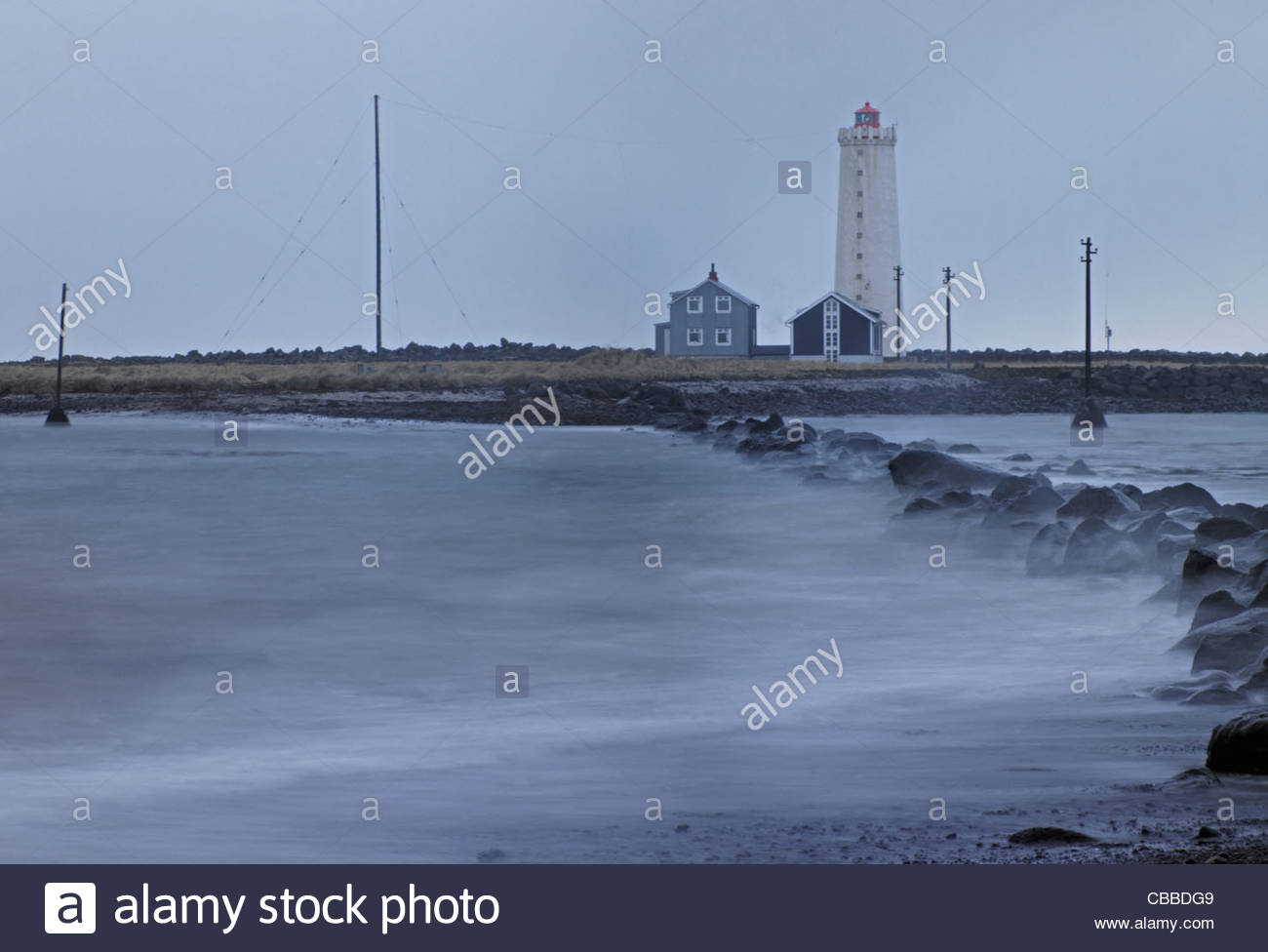 Waves crashing on rocks near lighthouse - Stock Image