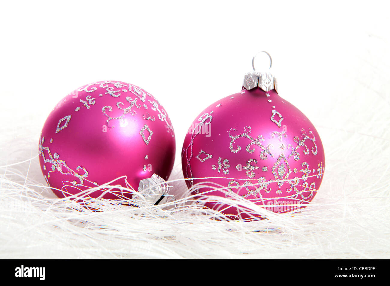 Two pink christmas balls with silver glitters over white background Stock Photo