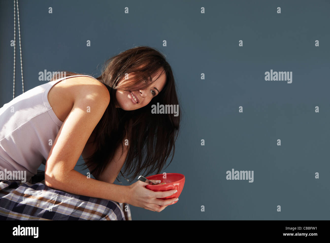 Smiling woman eating bowl of cereal - Stock Image