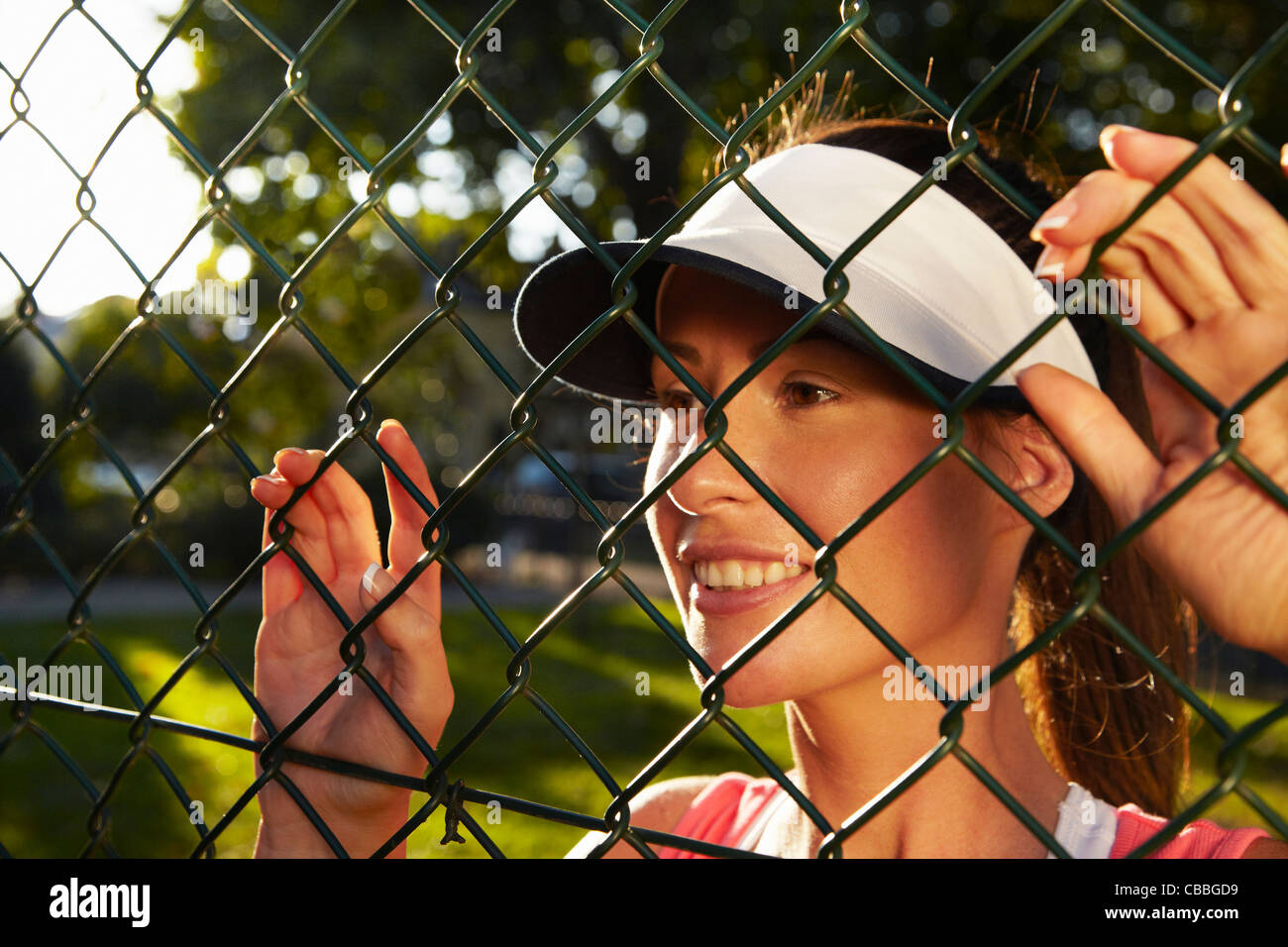 Woman peering through chain link fence - Stock Image