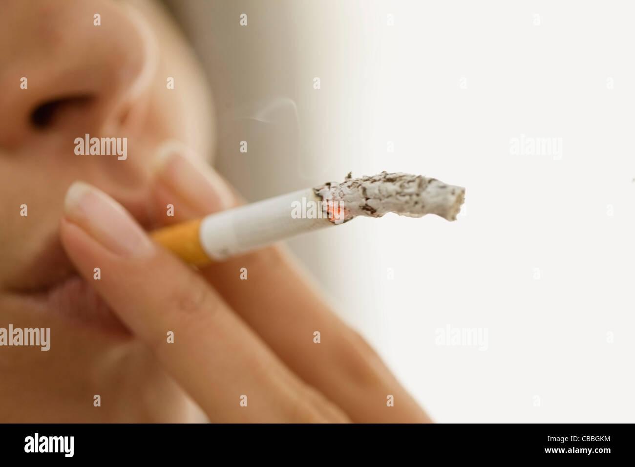 Close up of woman smoking cigarette - Stock Image