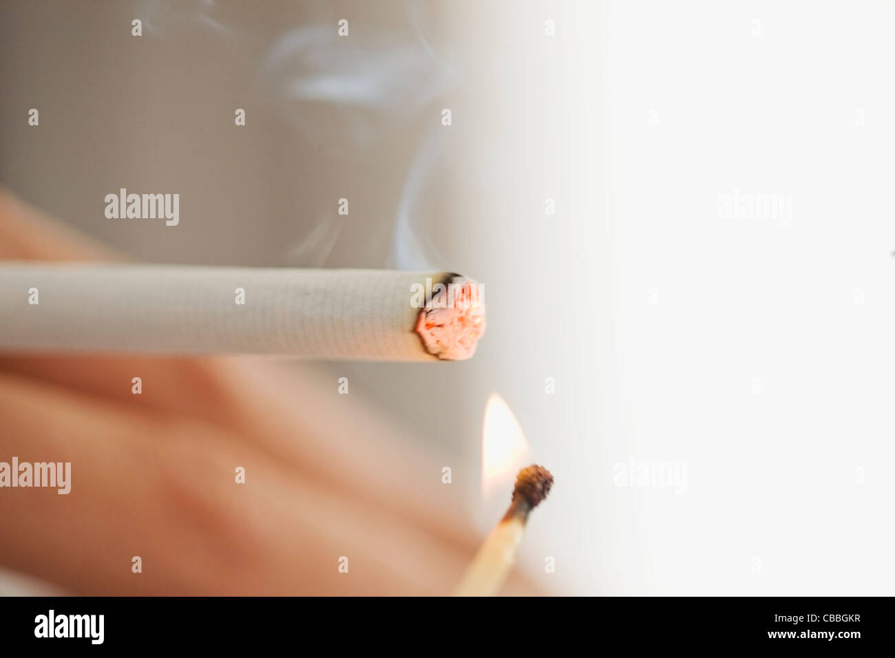 Close up of woman lighting cigarette - Stock Image