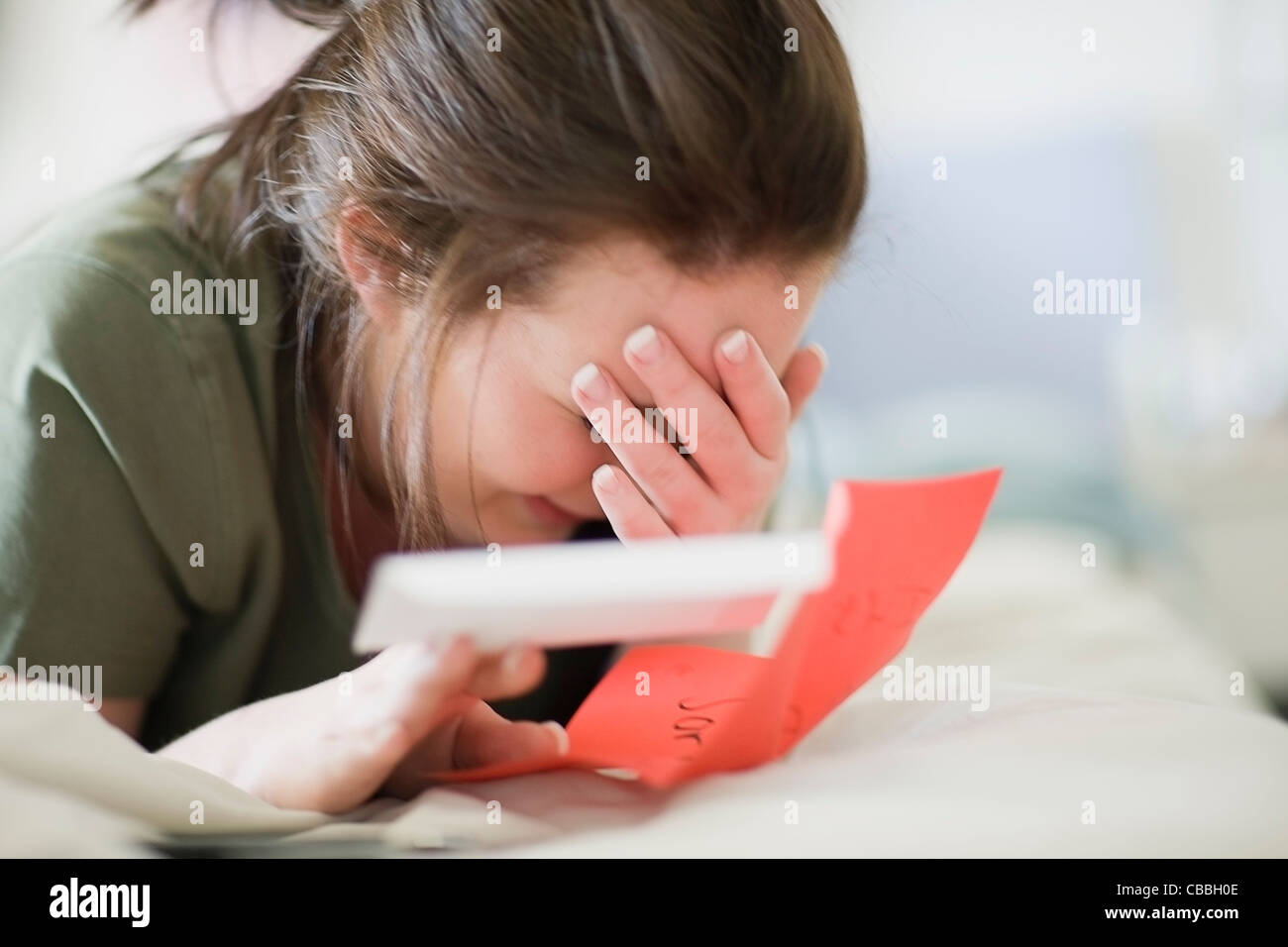 Crying teenage girl reading letter - Stock Image