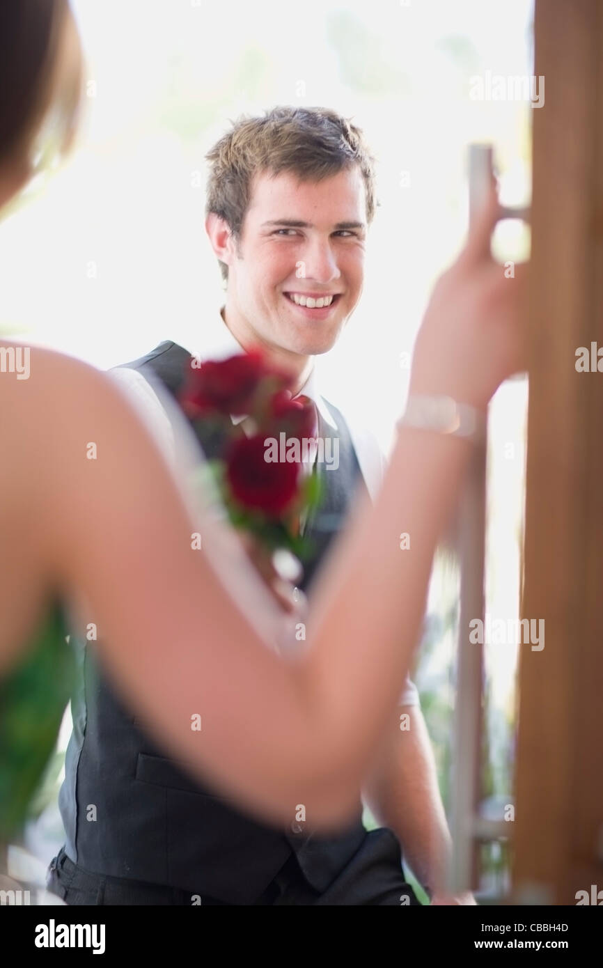 Teenage boy bringing flowers to date - Stock Image