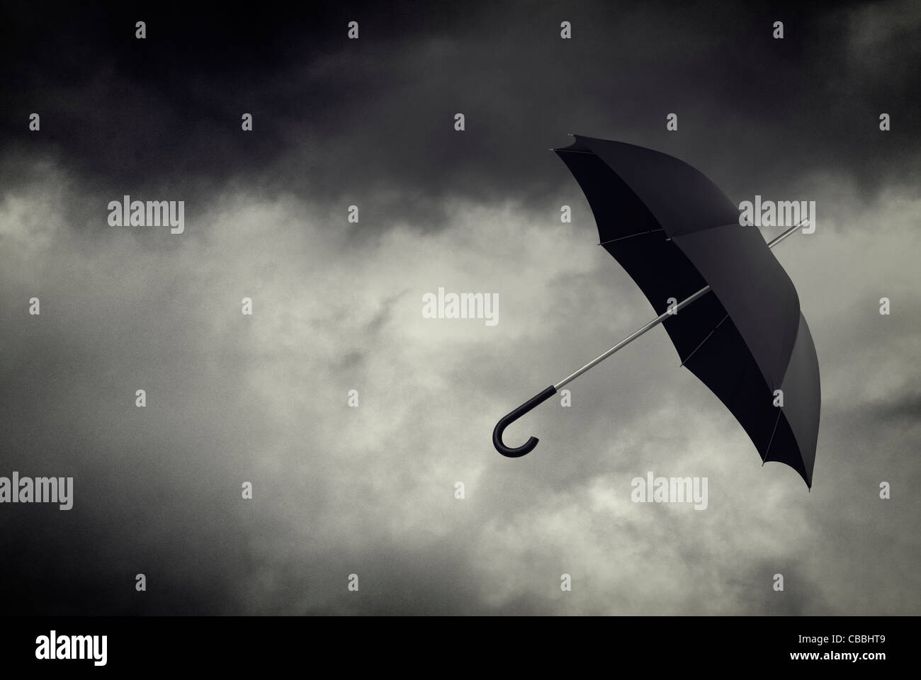 Umbrella floating in stormy sky - Stock Image