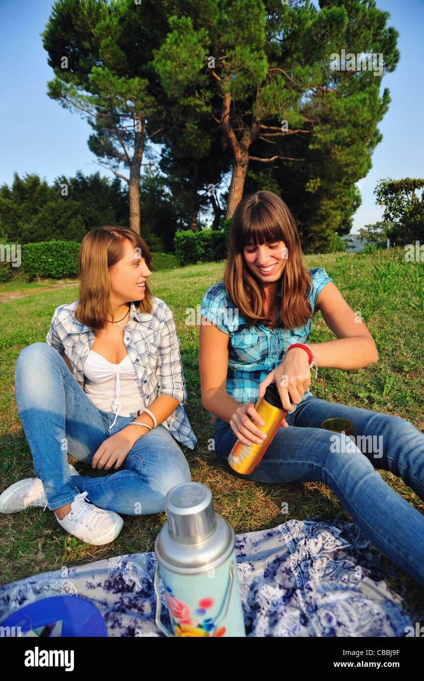 Teenage girls picnicking in rural field Stock Photo