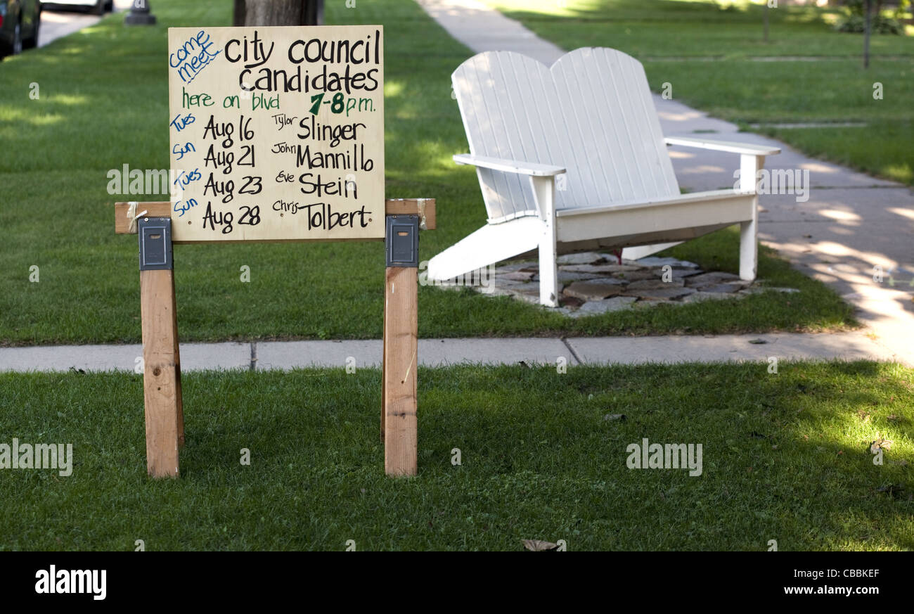 Yard sign with a list of dates to meet candidates running for public office - Stock Image