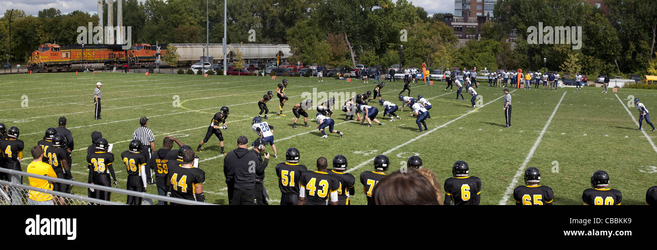 American high school football game being played outside with a Burlington Northern Santa Fe railroad train in the - Stock Image